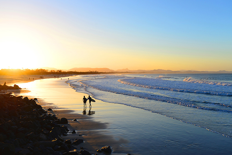 Surfers walk down the beach at sunset in Byron Bay, Australia