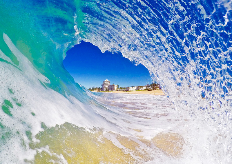 view from surfing under a cresting wave at Northern Beaches near Sydney, Australia