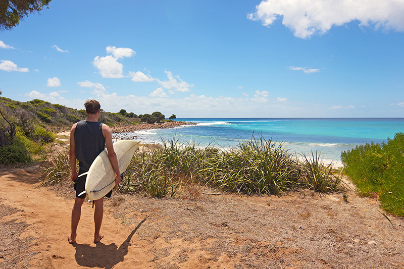 Surfer holding his surfboard on the beach in Margaret River, Western Australia