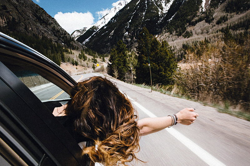 Girl leaning out of the car window - mountain scenery