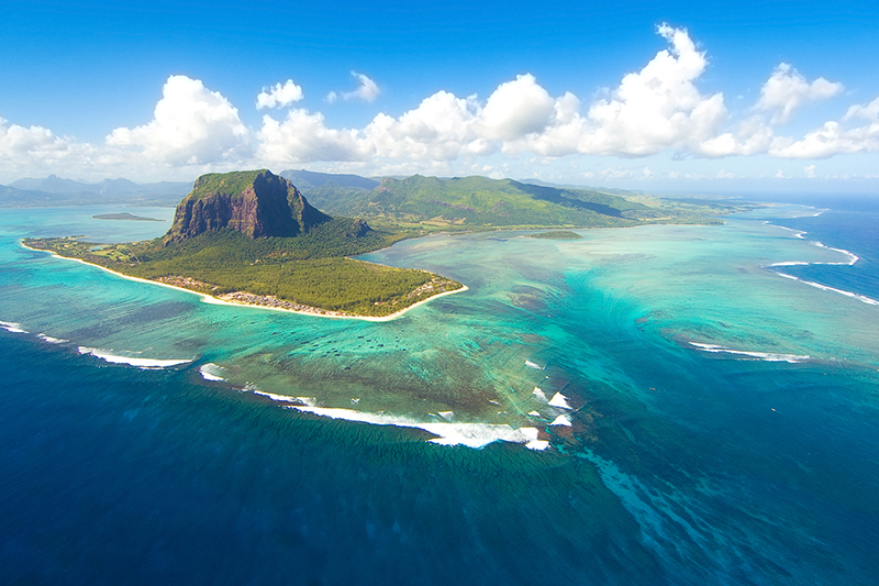 Aerial view of Mauritius with mountain and blue ocean.
