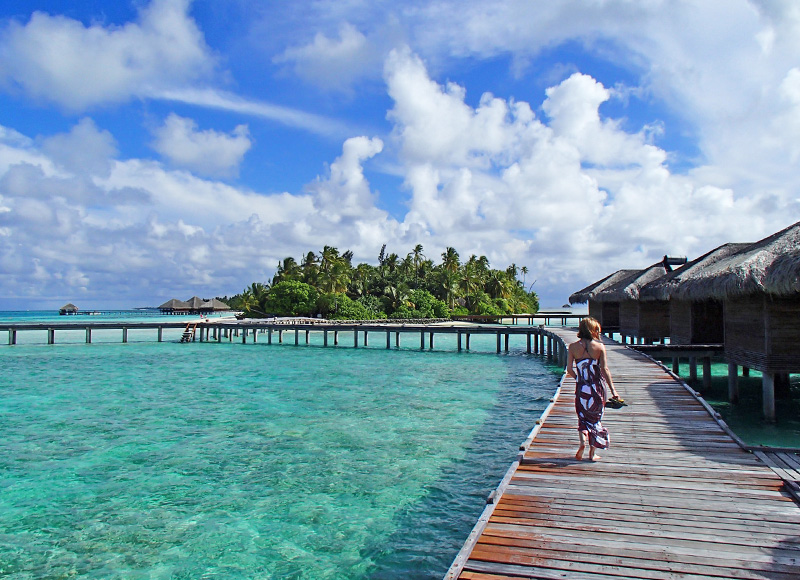 Eco-tourist walking on the boardwalk with crystal clear water in the Maldives