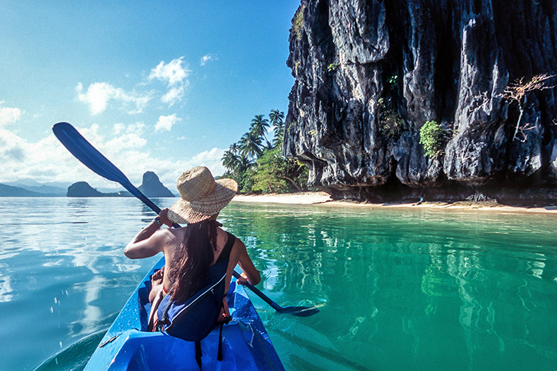 Sea-kayaking eco-traveller paddles through blue water in Palawan, El Nido, the Philippines
