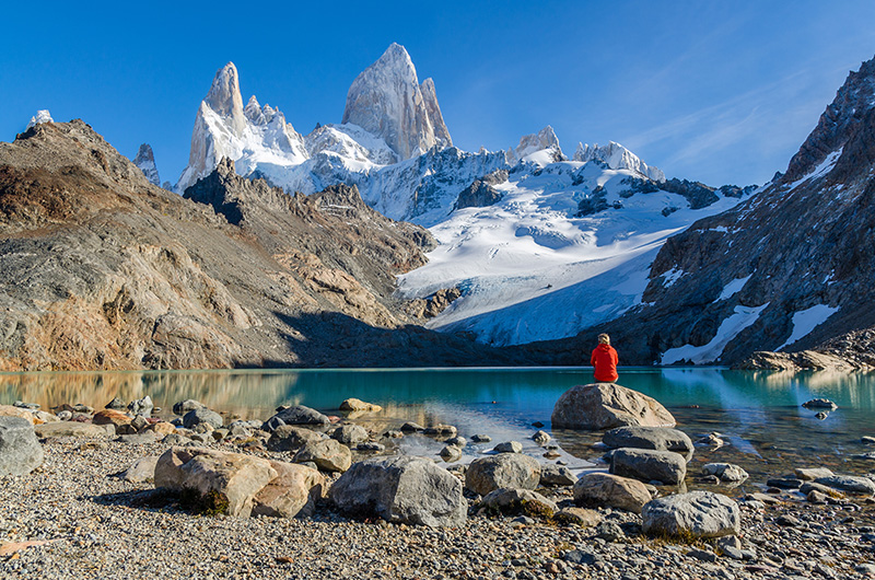 Eco-traveller sits in front of snow-capped mountain and blue lake - Patagonia, Chile
